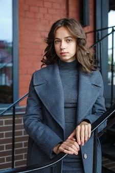 赤い建物の前で灰色のコートとタートルネックのポーズで若い思慮深いかわいい女の子