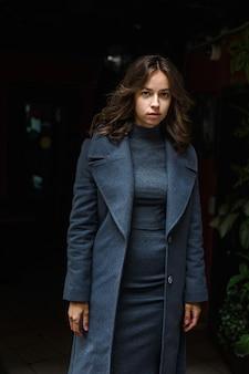 灰色のコートとタートルネックの若い思いやりのあるかわいい女の子が屋外でポーズします。魅力的な女性のストリートスタイルのポートレート写真撮影、美しいエレガントなモデルの都会的な写真撮影