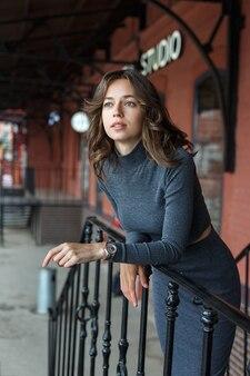 Молодая задумчивая красивая девушка в серой водолазке, юбка с часами на руке позирует перед красным зданием