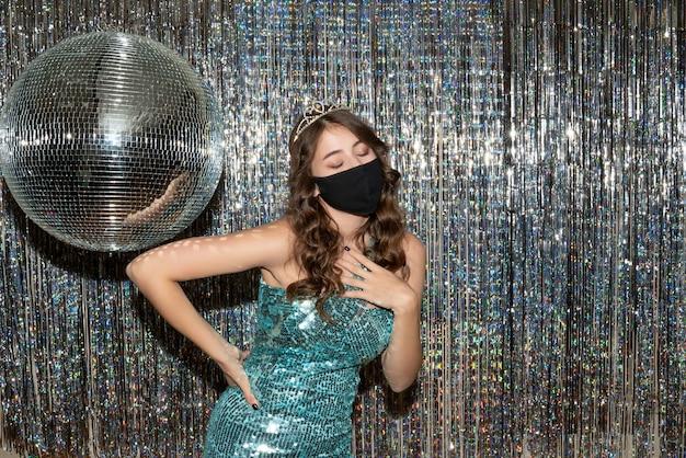 Giovane ragazza graziosa premurosa che indossa un abito lucido con paillettes con corona in maschera medica nera nel partito