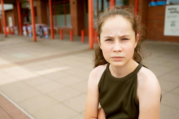 カメラを見ている若い思慮深い10代の少女、悲しい少女の屋外の肖像画