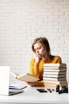 Молодая задумчивая женщина в желтом свитере учится с помощью ноутбука и читает книгу