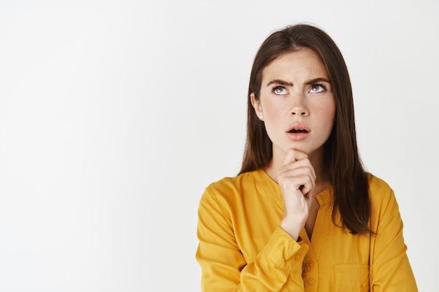 Молодая задумчивая женщина смотрит озадаченно, трогая подбородок, размышляя, ища решение, стоя над белой стеной