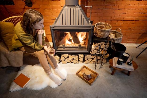 Молодая задумчивая женщина сидит у горящего камина, глядя на пламя в уютном доме