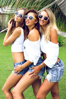 公園でポーズをとって、夏の時間に楽しんでいる若い3人の幸せな美しい女の子