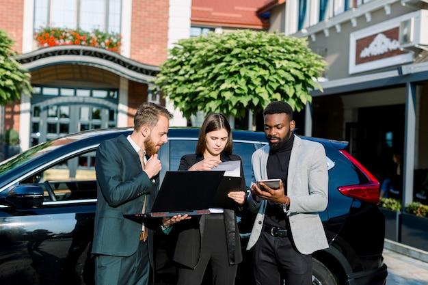 ノートパソコンとタブレットを使用してビジネスセンターで屋外の黒の新しい車の近くに若い3人の多民族ビジネス同僚。
