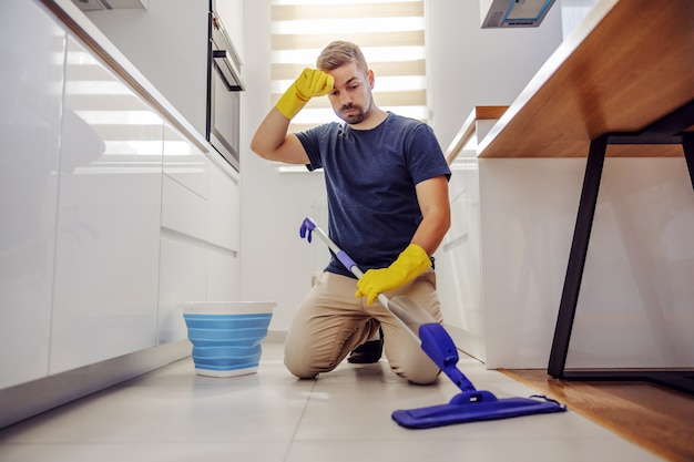 Young tidy worthy tired bearded man kneeling, wiping sweat and trying to clean dirty floor in kitchen.