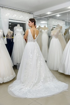 Young and tiny bride in wedding dress in salon