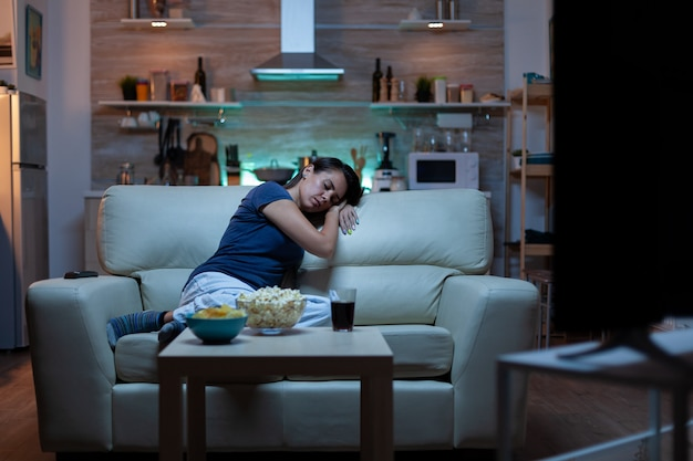Young tired after work woman looking asleep in the evening in front of tv. exhausted lonely sleepy lady in pajamas sleeping on sofa while watching a bored movie in living room, closing eyes at night