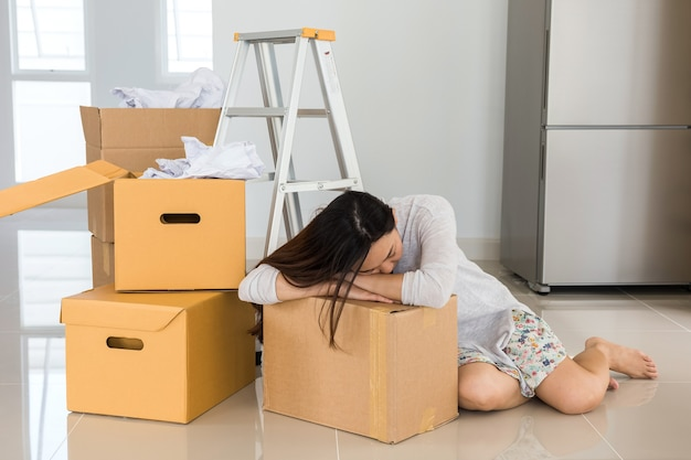 Young tired asian woman moving in new home, sit and sleep or nap on cardboard box. start new house's life. housing mortgage loan and refinance concept with copy space for text.