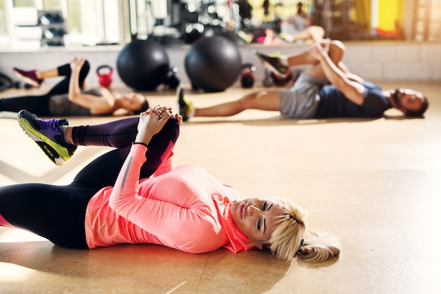 Young tired athletes in a gym stretching their leg muscles after pilates class.