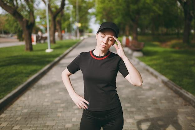 黒いユニフォームとキャップの若い疲れた運動美しいブルネットの女性が立って、休んで、走った後、頭の近くで手を保ち、屋外の都市公園でトレーニング