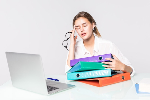 Young tired business woman with folders on office desk isolated on white background