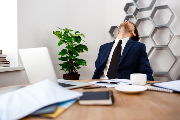 Молодой утомленный бизнесмен сидя на рабочем месте, предпосылка офиса.