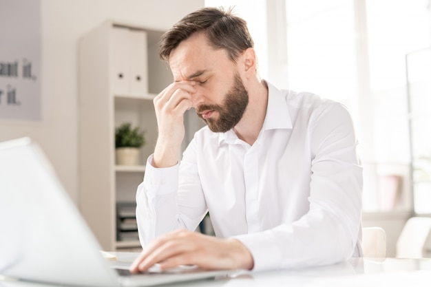 Young tired businessman in white shirt touching his nose bridge while slightly bending over desk during work