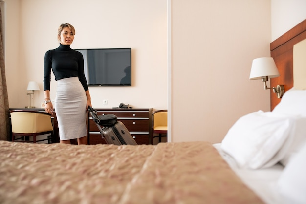 Young tired businesswoman with suitcase entering room after arriving to hotel and looking at comfortable bed