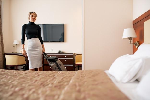 Молодая усталая деловая женщина с чемоданом входит в комнату после прибытия в отель и смотрит на удобную кровать