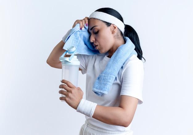 ヘッドバンドとリストバンドを身に着けている若い疲れた白人のスポーティな女性は横に立って、コピースペースで白いスペースに隔離された水のボトルを保持しているタオルで彼女の額を拭きます