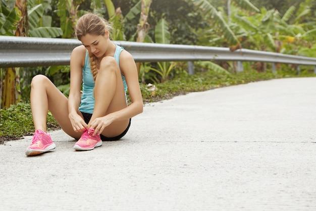 Giovane corridore caucasico stanco della donna che allaccia le sue scarpe da corsa rosa, seduto sulla strada nella foresta tropicale con una piccola pausa mentre fa jogging all'aperto.