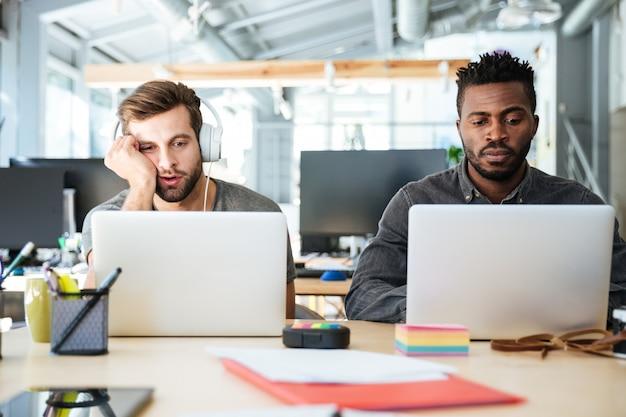 Молодые уставшие коллеги, сидя в офисе коворкинг