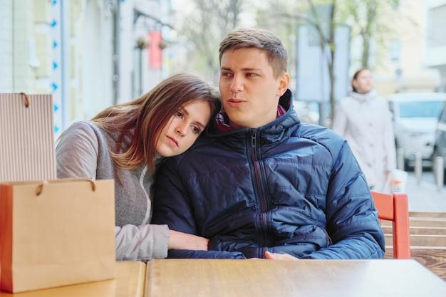 Молодая пара устали с сумок в уличных кафе