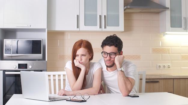 若い疲れているカップルが自宅の台所でラップトップを扱います。ホームビジネス、フリーランスのコンセプト