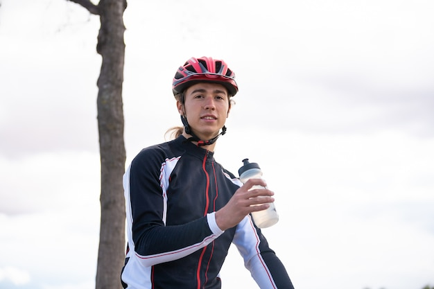Young tired cyclist drinking water in park