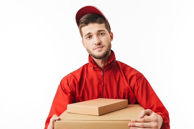 Young tired delivery man in red cap and jacket holding boxes in hands thoughtfully
