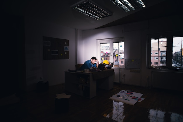 Young tired disappointed business man searching for problem solution on a laptop while staying after regular working time in the dark office.