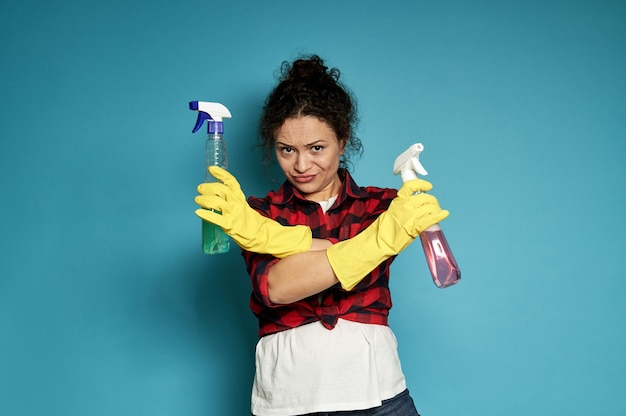 若い疲れた疲れ果てた不満を持った主婦は、手に掃除用スプレーを持って、否定して腕を組んだ。