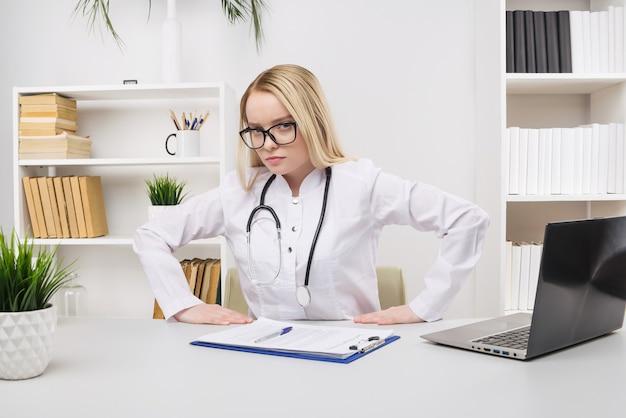 机に座って、病院のライトオフィスで医療文書を使用してコンピューターで作業している若い疲れた疲れた女性。医療用ガウンの女性医師が診察室で眠るヘルスケア医学の概念