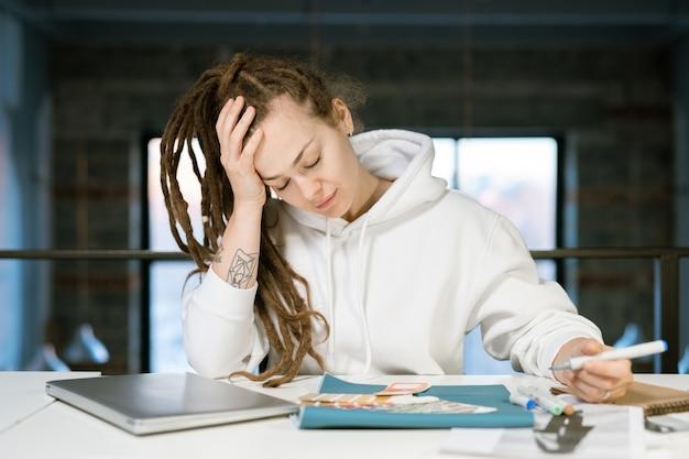 책상 위로 구부리고 새 컬렉션의 색상을 선택하는 동안 그녀의 머리를 만지고 젊은 피곤 여성 디자이너