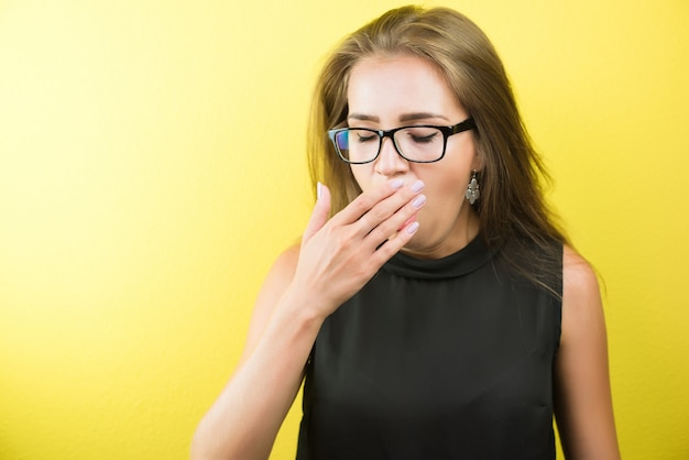 Young tired female office worker wearing spectacles and yawning