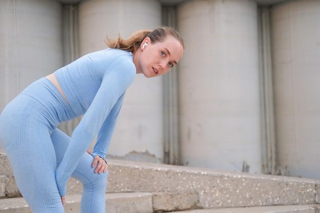 젊은 지친 피트니스 여성이 도시에서 달리기를 마칩니다. 음악을 듣다. 일몰. 건강한 생활. 자유. 야외 운동. 고품질 사진