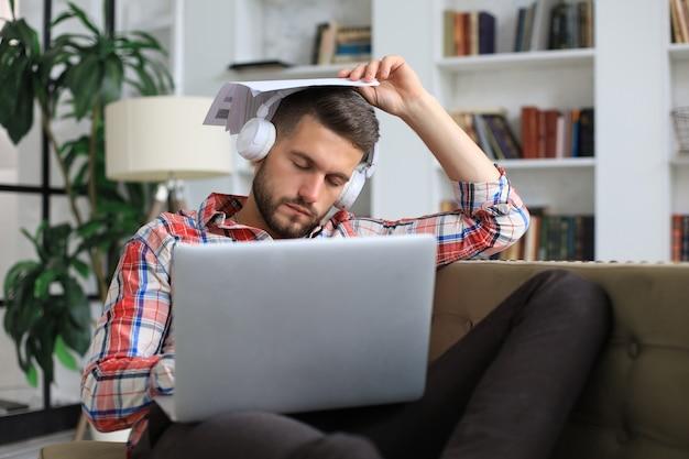 ノートパソコンの前のソファに座っているカジュアルウェアの若い疲れたフリーランサー。