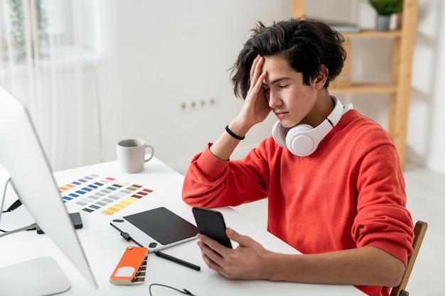 Молодой усталый фрилансер трогает голову во время использования смартфона перед компьютером в домашней среде