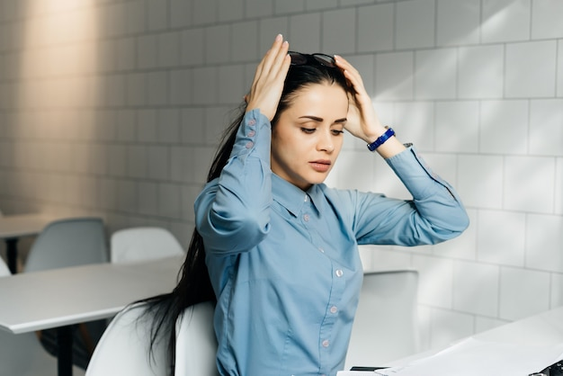 Young tired girl freelancer in blue shirt works a lot