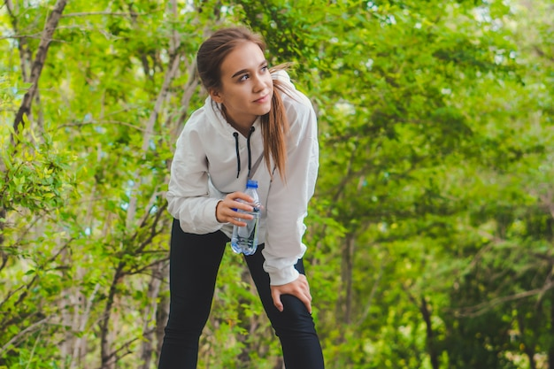 Young tired happy caucasian girl drinking water in park while jogging. copy space