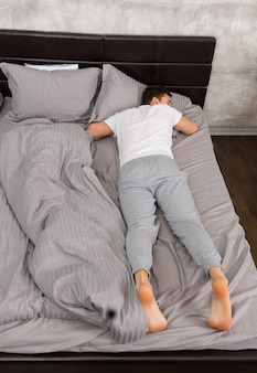 회색 색상의 세련된 침대와 로프트 스타일의 침실에 촛불이 있는 침대 옆 탁자 근처에서 담요 없이 잠자는 잠옷을 입은 피곤한 젊은 남성