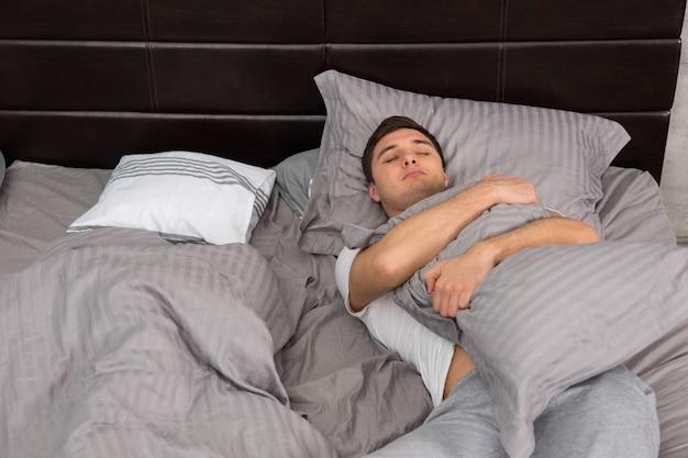 잠옷을 입은 피곤한 젊은이는 담요 없이 혼자 자고 회색 색상의 세련된 침대에서 베개를 껴안고 로프트 스타일의 침실에 촛불이 있는 침대 옆 탁자 근처에 있습니다.
