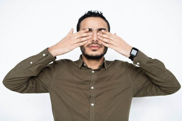 Young tired man in shirt covering his eyes by hands at break between work while relaxing in isolation