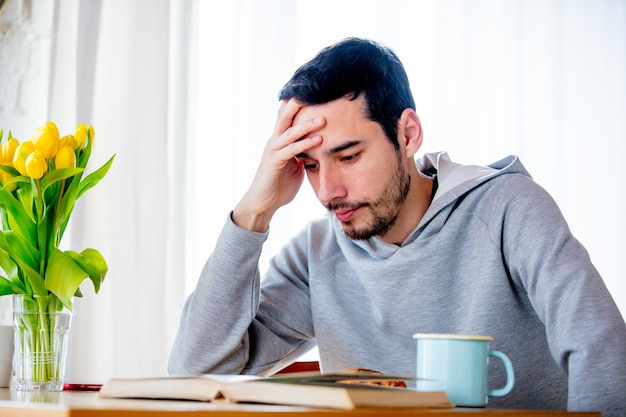 Young tired man sitting at table with cup of coffee or tea and book. kitchen location.
