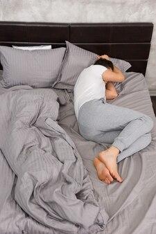 회색 색상의 세련된 침대와 로프트 스타일의 침실에 촛불이 있는 침대 옆 탁자 근처에서 담요 없이 자는 젊은 피곤한 남자