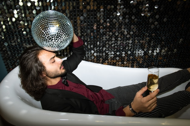 Young tired man with disco ball by head and flute of champagne relaxing in bathtub at party in the night club