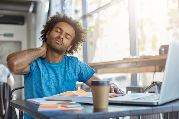 서류와 노트북 컴퓨터로 둘러싸인 레스토랑에 앉아 젊은 피곤 관리자는 졸리고 피곤한 그의 눈을 감고 고통을 목에 그의 손을 잡고 피곤 표정을 가지고 있습니다. 피곤함