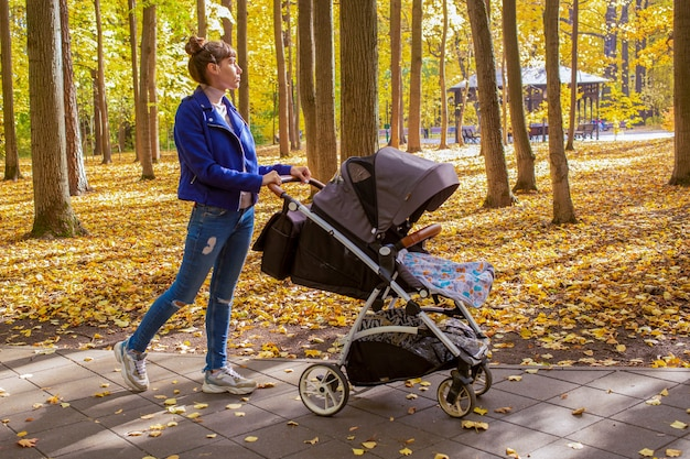 Young tired mother goes with a stroller in autumn park infant baby is sleeping in a carriage