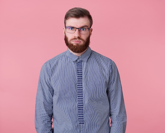 Молодой уставший от работы рыжебородый парень в очках и полосатой рубашке смотрит вдаль, думает, сколько еще проектов закрыть и успеет ли он, изолировавшись на розовом фоне.