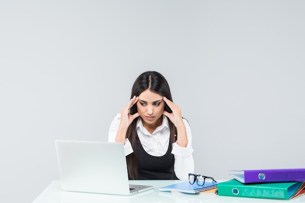 Young tired, onworked and exhausted female office worker in grey suit on white