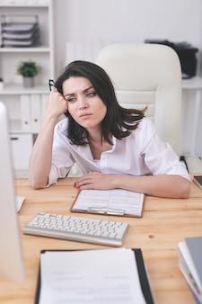 Молодая уставшая или раздраженная бизнес-леди сидит за столом перед экраном компьютера, ожидая загрузки онлайн-страницы