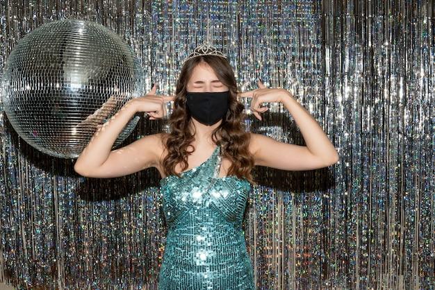 Giovane ragazza carina stanca che indossa un abito lucido con paillettes con corona nella mascherina medica nera nel partito